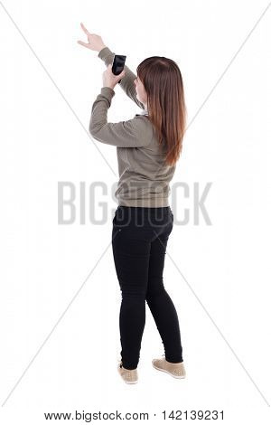 back view of pointing young beautiful  woman and using a mobile phone. girl  watching. Rear view people collection.  backside view of person.  Isolated over white background. A girl in a gray sweater