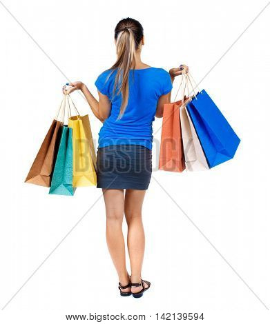 back view of woman with shopping bags. backside view of person.  Rear view people collection. Isolated over white background. girl in a short skirt and a blue shirt holding colored bags with purchases