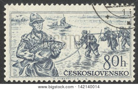 MOSCOW RUSSIA - CIRCA APRIL 2016: a post stamp printed in CZECHOSLOVAKIA shows a fisherman with a fish in his hands the series