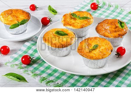 French dish julienne. Mushroom chicken and cheese gratin in Aluminum Foil Mini Baking molds decorated with basil leaves and cherry tomatoes on white plate authentic recipeclose-up