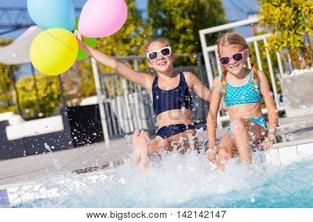 Two happy children with balloons playing on the swimming pool in aqua park at the day time. Concept of friendly family.