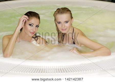 Portrait of a two young adult attractive sexy and sensuality pretty beautiful brunette girls in jacuzzi