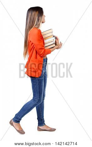 Girl comes with  stack of books. side view. Rear view people collection.  backside view of person.  Isolated over white background. girl in a red jacket goes to the side with a stack of books looking