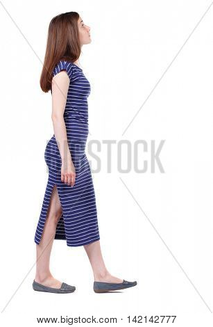 back view of walking  woman. beautiful girl in motion.  backside view of person.  Rear view people collection. Isolated over white background. The brunette in a blue striped dress goes to the side