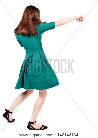 skinny woman funny fights waving his arms and legs. Isolated over white background. The slender brunette in a green short dress causes a sharp blow.