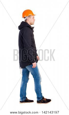 Back view of walking engineer in helmet.  Rear view people collection. Backside view of person. Isolated over white background. Engineer in warm clothing thoughtfully goes right