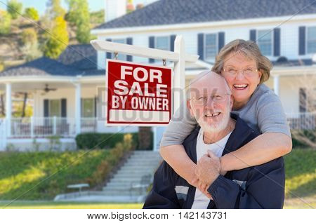 Senior Adult Couple in Front of Home For Sale Real Estate Sign and Beautiful House.