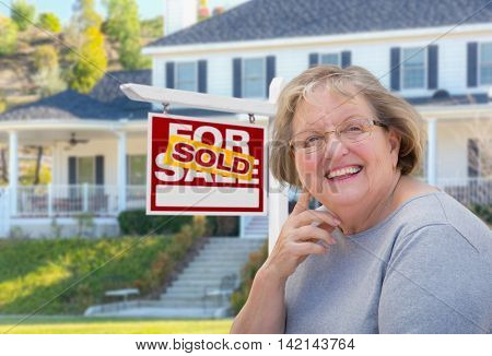 Senior Adult Woman in Front of Sold Home For Sale Real Estate Sign and Beautiful House.