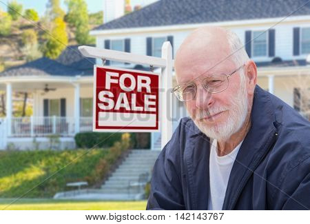 Senior Adult Man in Front of Home For Sale Real Estate Sign and Beautiful House.