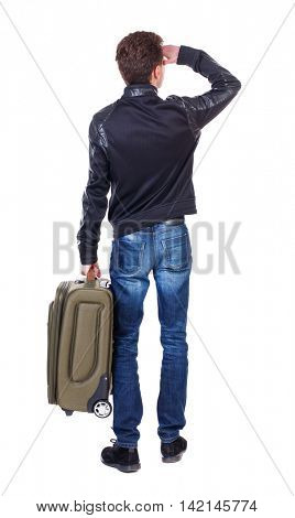 Back view of man with  green suitcase looking up. Rear view people collection.  backside view of person.  Isolated over white background. A traveler is standing with a suitcase in his hand and looks