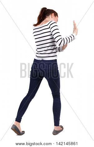 back view of woman pushes wall.  Isolated over white background. Rear view people collection. backside view of person. Girl in a striped sweater pushing something in front of him.
