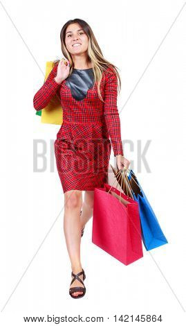 front view of a woman jumping with shopping bags. beautiful brunette girl in motion.  front view of person.  Isolated over white background. The girl in red plaid dress comes to meet us smiling and