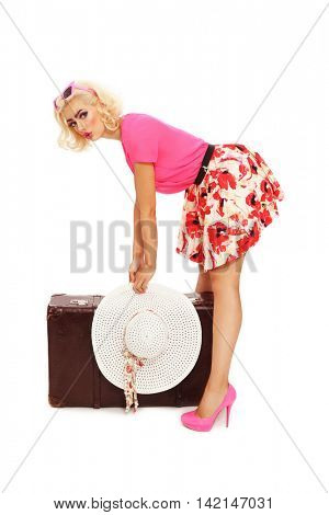 Beautiful sexy blonde pin-up girl in mini skirt and hot pink shoes holding in her hands big heavy vintage bag over white background