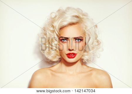 Vintage style portrait of young sexy beautiful platinum blonde woman with stylish hairdo and red lips