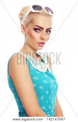 Young beautiful tanned blonde woman in vintage dress and sunglasses over white background