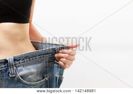 Young Woman Delighted With Her Dieting Results On White Background,a Slim Woman Is Showing How Much
