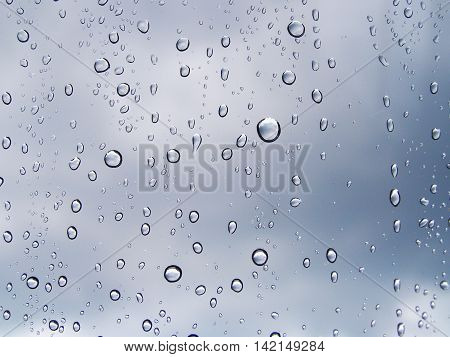Water drops on the glass window with the reflection of cloud in every raindrops