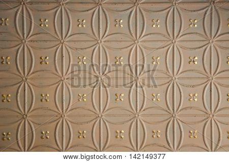 Closeup abstract of ornate textured ceiling with golden accents and repeating pattern.