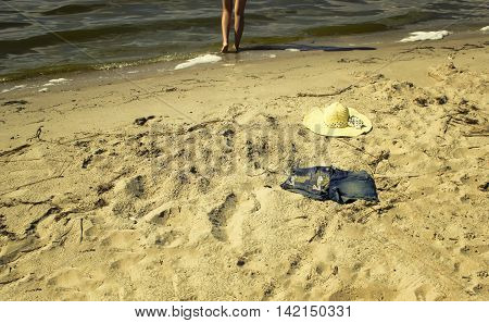 The hat and shorts lying on the sand at the beach near the sea. Women's legs in the background in water