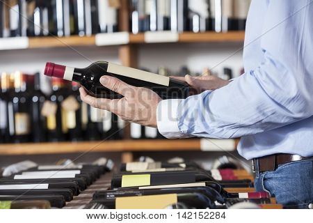 Midsection Of Customer Holding Red Wine Bottle