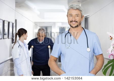 Doctor With Hands In Pockets Standing With Colleague And Patient