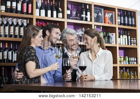 Friends Enjoying Wine At Counter In Winery