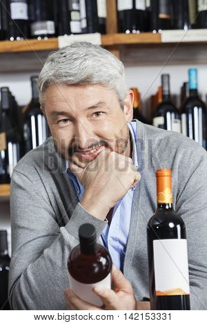 Mature Man With Hand On Chin Holding Wine Bottle