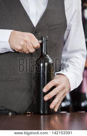 Midsection Of Bartender Opening Wine Bottle