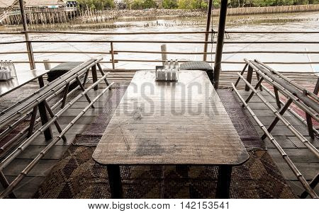 Inside of the riverside restaurant having a wood table Thai style seat.