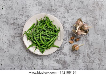 French bean in white plate on the rough light gray surface with garlic top view. Ingredients for making helpful vegetarian food