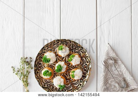 Crackers with cheese cream and parsley, free space, flat lay. Appetizing regale snack, served on beautiful plate on white wooden background. Copy space for text