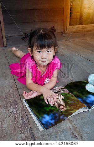 Closeup asian girl smiling and reading picture album lying on wooden floor with bright sunlight outdoor at home. Children read and study education concept.