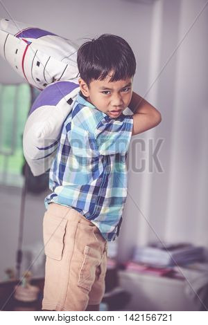 An aggressive asian child. Boy looking furious. Kid will throw pillow inside bedroom. Negative human face expressions emotions problem families concept. Vintage tone.