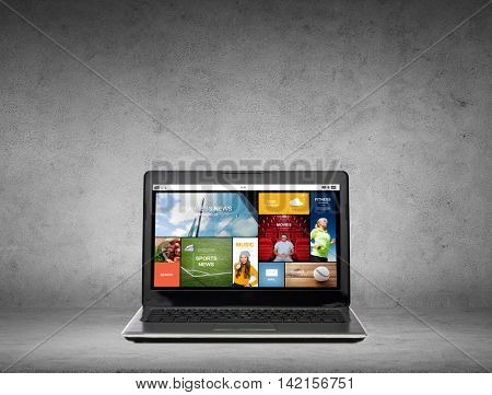 technology and mass media concept - laptop computer with internet news web page on screen over gray concrete background