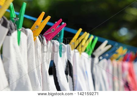Drying clothes hanged on the clothesline securing with color clothespins.