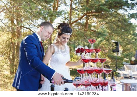 Newlyweds are pouring vine in the pyramid of glasses at the open air wedding banquet
