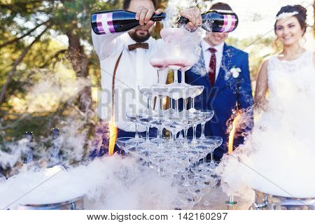 Bartender with newlyweds are pouring vine in the pyramid of glasses at the open air wedding banquet