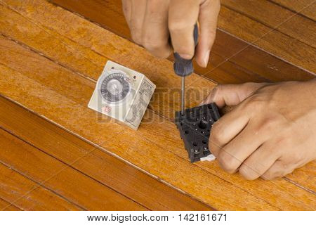 Man repairing equipment of farm on wooden background.