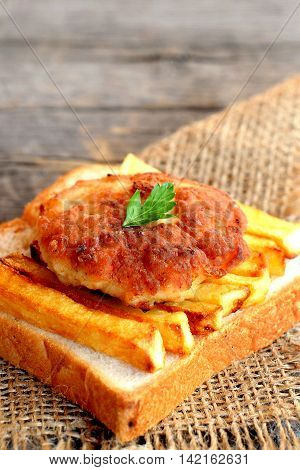 Sandwich with fried potatoes and minced meat cutlet on a burlap and on old wooden table. A sandwich cooked from slice of white bread, deep fried potatoes and Turkey cutlet