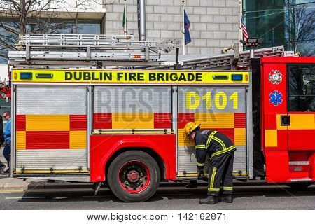 Firefighter in front of a fire engine.  Dublin city, Ireland - April 21, 2016: Irish firefighter from Dublin fire brigade in front of fire engine.  Irish firefighter and fire engine