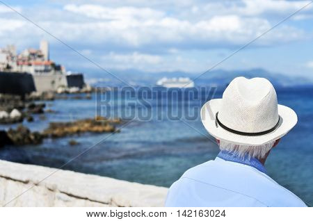 an old caucasian man seen from behind looking at the sea in Antibes, France, with a filter effect