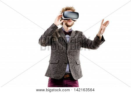 Young curly-haired businessman wearing brown suit use a VR headset and experiencing virtual reality isolated on white background