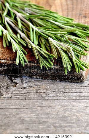 Fresh green rosemary sprigs on a cutting board and an old wooden background with blank space for text. Fragrant herb used in cooking, medicine, cosmetics. Closeup