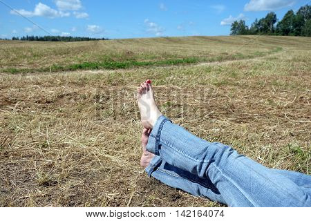 Side view  of beautiful playful female bare feet with red nails in rolled blue jeans resting on meadow under summer day sky with white clouds