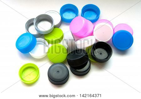 Bunch of multicolored used plastic bottle caps on white background