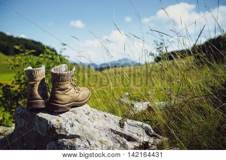 Old hiking boots on rock in the mountains