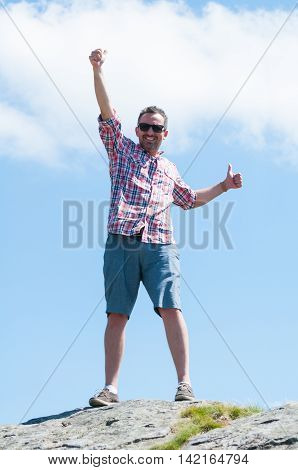 Male Backpacker Feeling Victorious On Top Of The Mountain