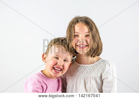 Boy and girl holding each other, sibling love portrait.