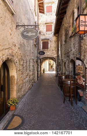TORRI DEL BENACO - MAY 4, 2016: Old street and picturesque houses of Torri del Benaco. Garda Lake Italy