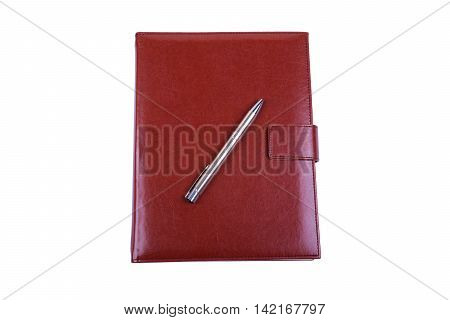 Red leather diary and ball pen isolated on white